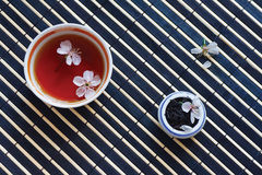 Cup of tea, jar of tea leaves and cherry blossoms Stock Photos