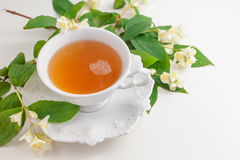 Cup of tea with jasmine flowers on a white table Royalty Free Stock Image