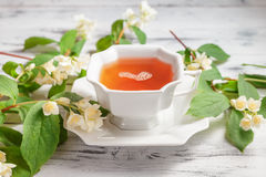 Cup of tea with jasmine flowers on a white table Royalty Free Stock Images