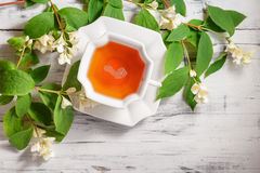 Cup of tea with jasmine flowers on a white table Stock Image