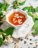 Cup of tea with jasmine flowers on a white table Stock Photography