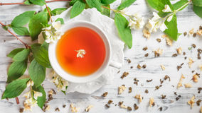 Cup of tea with jasmine flowers on a white table Royalty Free Stock Photo