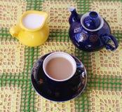 Cup of tea jug with milk and teapot. Crockery on knitted cloth.cup of tea jug with milk and teapot Stock Image