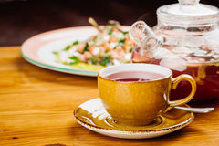 Cup of tea and kettle  on wooden background Stock Photography