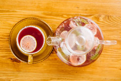 Cup of tea and kettle  on wooden background Royalty Free Stock Photography
