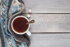 A cup of tea and a knitted scarf on the background of a white wo Stock Image
