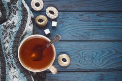 A cup of tea, a knitted scarf and bagels on the background of a. A cup of tea, a knitted scarf and bagels on the background of blue wooden table stock photos