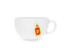 Cup tea label SriLanka. Cup of Ceylonese tea with teabag label in the form of Sri Lanka map in national flag colours as symbol of one of the world best maker of Royalty Free Stock Images