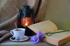 Cup of tea, lantern, book Stock Image