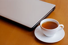 Cup of tea and laptop Stock Image