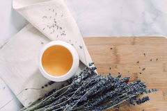 Cup of tea with lavender on a piece of cloth. Cup of tea with lavender on a wooden breadboard. Blue, white, yellow colours.Marble table Royalty Free Stock Photography