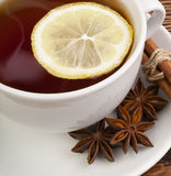 Cup of tea with lemon. Hot cup of tea with lemon and spices on a wooden table Royalty Free Stock Photos