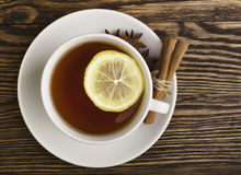 Cup of tea with lemon. Hot cup of tea with lemon and spices on a wooden table Royalty Free Stock Photography
