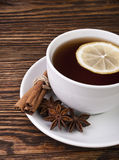 Cup of tea with lemon. Hot cup of tea with lemon and spices on a wooden table Stock Photography