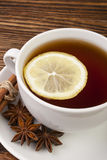 Cup of tea with lemon. Hot tea with lemon and spices on a wooden table Royalty Free Stock Photos