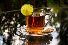 A cup of tea with lemon. And biscuits on a glass table Royalty Free Stock Images