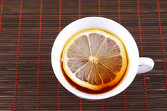 Cup of tea with a lemon on bamboo napkin Royalty Free Stock Images