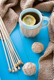 A cup of tea with lemon, beige knitted blanket and spokes Stock Images