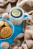 A cup of tea with lemon, biscuits, beige knitted blanket Royalty Free Stock Photography