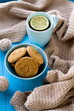 A cup of tea with lemon, biscuits, beige knitted blanket Stock Photos