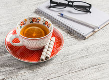 Cup of tea with lemon, biscuits and an open blank notebook. On a light wooden table Stock Image