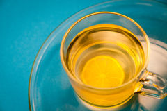 Cup of Tea with Lemon on blue Background. Fresh glass of herbal tea with lemon on blue background Stock Images