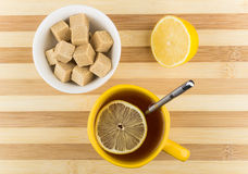 Cup of tea with lemon and bowl of lumpy sugar Royalty Free Stock Image