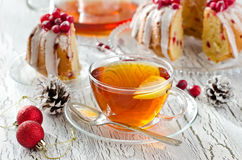 Cup of tea with lemon and cranberry cake for christmas. With decoration on white wooden background Royalty Free Stock Photo