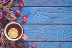 A cup of tea with lemon and flowers on the background of a blue Royalty Free Stock Photography