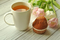 A cup of tea with lemon, fresh tulips and appetizing cake Stock Photography