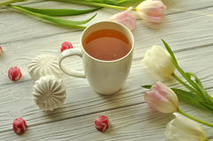 A cup of tea with lemon, fresh tulips and appetizing sweets Royalty Free Stock Image