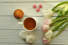 A cup of tea with lemon, fresh tulips and appetizing sweets Stock Photography