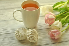 A cup of tea with lemon, fresh tulips and appetizing sweets Royalty Free Stock Photography