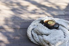 Cup of tea with lemon, knitted scarf near at wood background outdoor. Outdoor composition. White cup with tea and lemon, knitted scarf and nuts near, on wood royalty free stock images