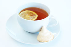 Cup of tea with lemon and meringue cookie. On white background. Focus on the tea Stock Images