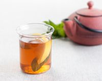 Cup of tea with lemon and mint. Teapot in the background Stock Photo