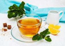Cup of tea with lemon and mint. On a old white wooden background Royalty Free Stock Images