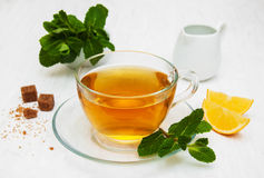 Cup of tea with lemon and mint. On a old white wooden background Stock Image