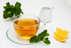 Cup of tea with lemon and mint. On a old white wooden background Stock Photography