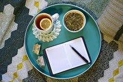 Cup of tea with lemon, natural herbal tea and notebook with pen stock photography