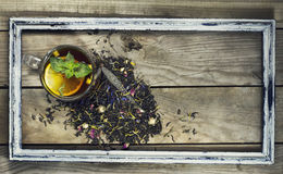 Cup of tea with lemon in an old frame. Cup of tea with lemon and mint in an old frame on a wooden background stock photos