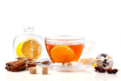Cup of tea with lemon over white. Cup of tea with lemon and spices, served with tea strainer isolated over white. See series royalty free stock image