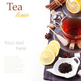 Cup of tea with lemon over white. Cup of tea with lemon and spices, served with tea strainer over white with sample text Royalty Free Stock Photos