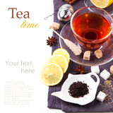 Cup of tea with lemon over white. Cup of tea with lemon and spices, served with tea strainer over white with sample text. See series royalty free stock photo