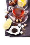 Cup of tea with lemon over white. Cup of tea with lemon and spices, served with tea strainer over white. See sries stock images