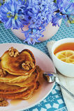 Cup of tea with lemon, pancakes with honey and walnuts on a plate. Purple hyacinths in a vase Stock Images