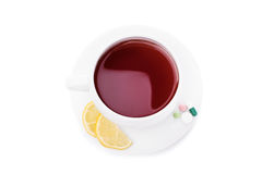 Cup of tea with lemon and pills. Cup of tea with slices of lemon and some pills isolated on white background Stock Photo