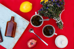 A cup of tea, lemon on a red background, food and drink, knife and fork, tea time, breakfast time view from above, cup of coffe, r. Ed apples , a bouquet of Royalty Free Stock Image