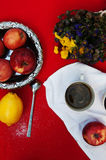 A cup of tea, lemon on a red background, food and drink, knife and fork, tea time, breakfast time view from above, cup of coffe, r. Ed apples , a bouquet of Stock Image