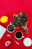 A cup of tea, lemon on a red background, food and drink, knife and fork, tea time, breakfast time view from above, cup of coffe, r. Ed apples , a bouquet of Royalty Free Stock Photography